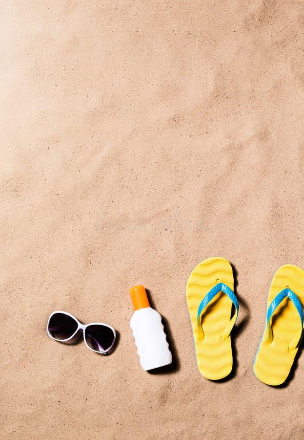 Sandaler för Flipmisslyckande, solglasögon och sunscreen, sandstrand arkivbild