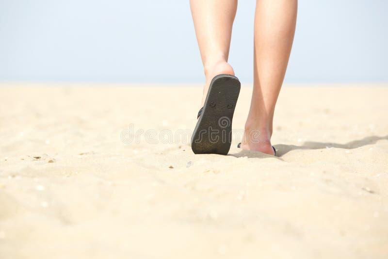Sandaler som går på sand på stranden royaltyfri bild