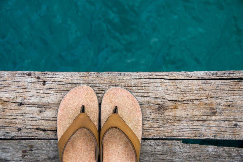 Sandales beiges de bascule sur le bord du dock en bois au-dessus de l'eau images stock