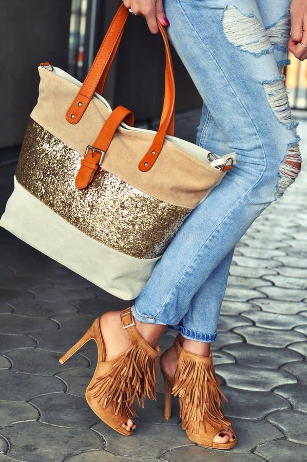 Sandales de port de talon haut de femme à la mode avec la frange, les jeans et le sac photo stock