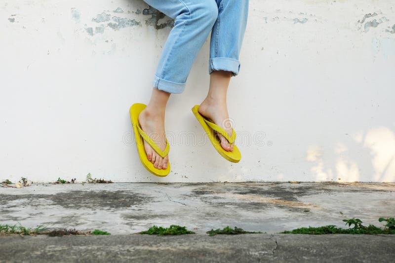 Sandales jaunes Femme utilisant Flip Flops et des blues-jean se tenant sur le vieux plancher de ciment images stock