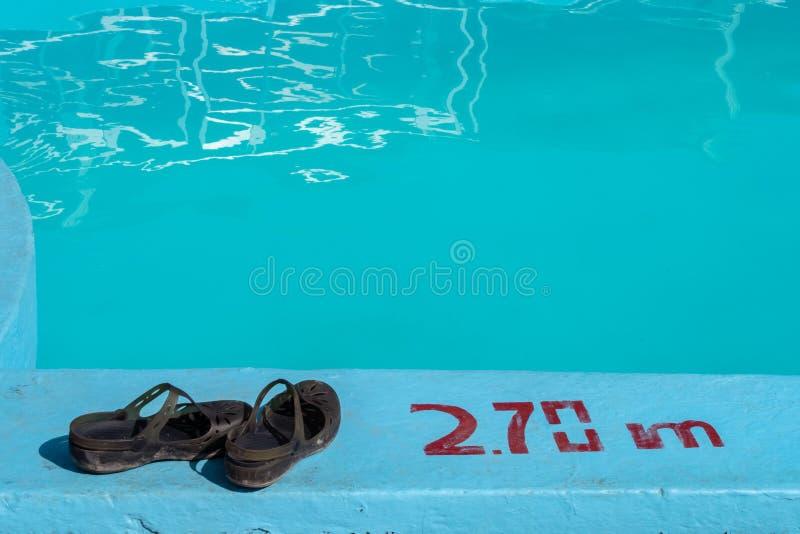 Sandales par une piscine avec 2 inscription de profondeur de 70m photographie stock libre de droits