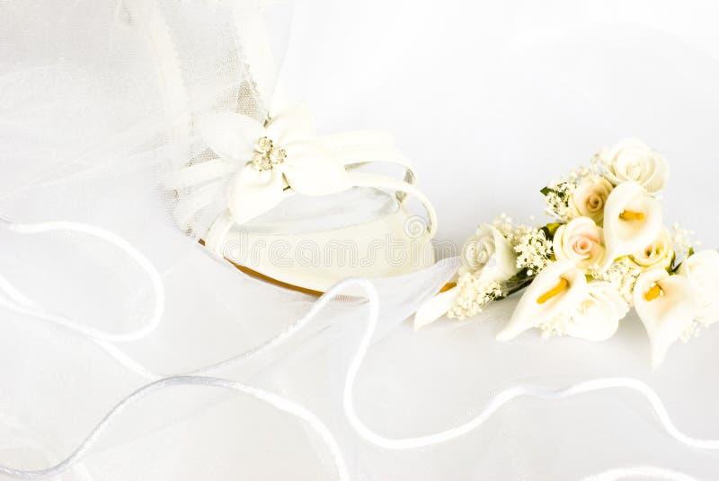 Sandali e fiori di cerimonia nuziale sopra il velare fotografie stock libere da diritti