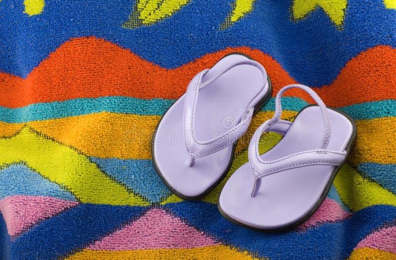 Sandali infantili della ragazza sul tovagliolo di spiaggia fotografia stock