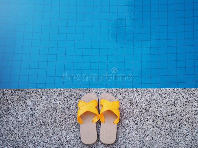Sandalia amarilla por la piscina foto de archivo