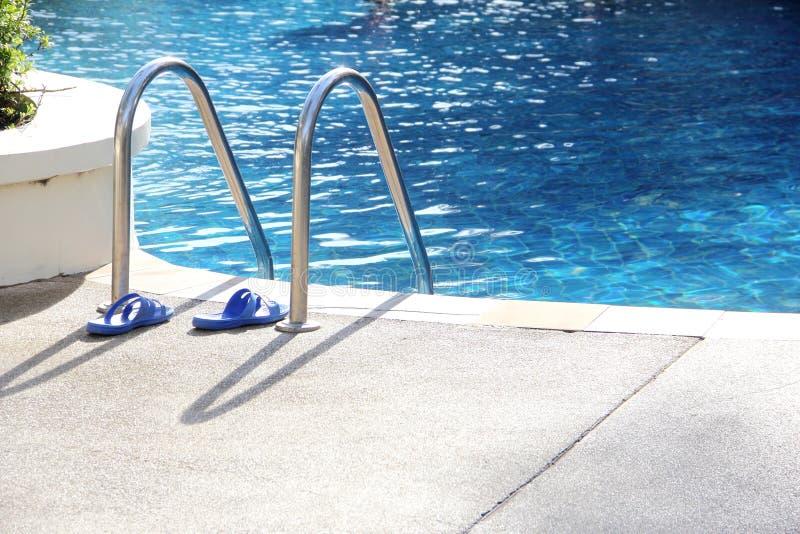Sandalia cerca de la escalera de la piscina fotos de archivo
