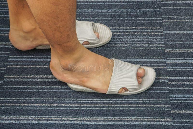 Sandalia demasiado apretada del desgaste de hombres en sus pies en la casa imagenes de archivo