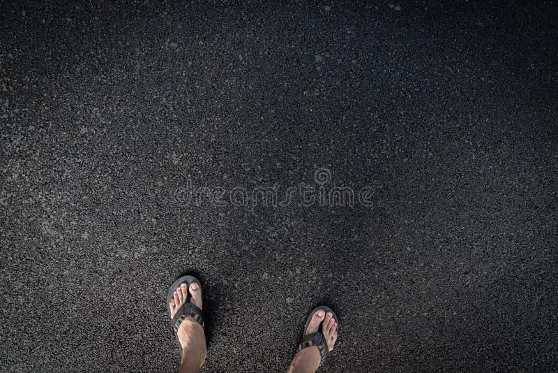 Sandalia en el camino del asfalto imagenes de archivo