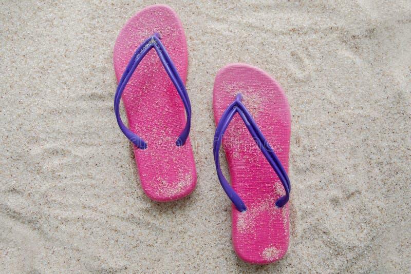 Sandalia rosada en la playa arenosa imagenes de archivo