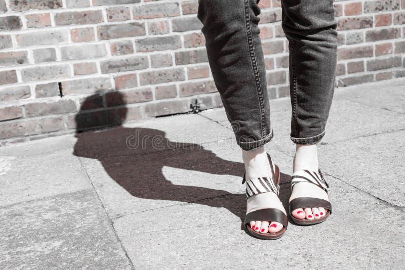 Sandalias blancos y negros que llevan modelo con el estampado de zebra foto de archivo