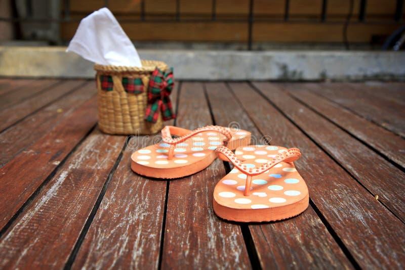 Sandalias coloridas de la chancleta en el fondo de madera fotos de archivo