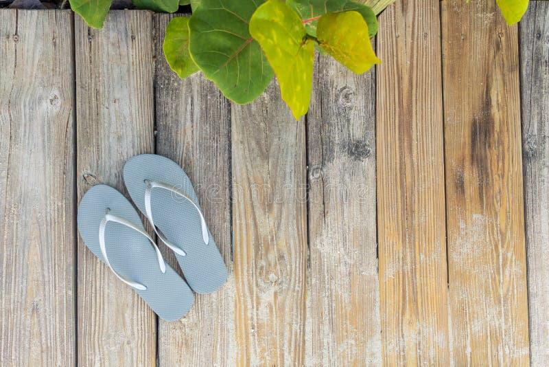 Sandalias de Flip Flop en un paseo marítimo del lado de la playa arenosa foco hacia n?meros m?s inferiores y medios foto de archivo
