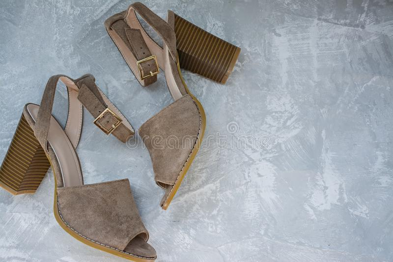 Sandalias del beige del ` s de las mujeres Calzado del verano Fondo ligero Fondo debajo del hormig?n Espacio para el texto foto de archivo
