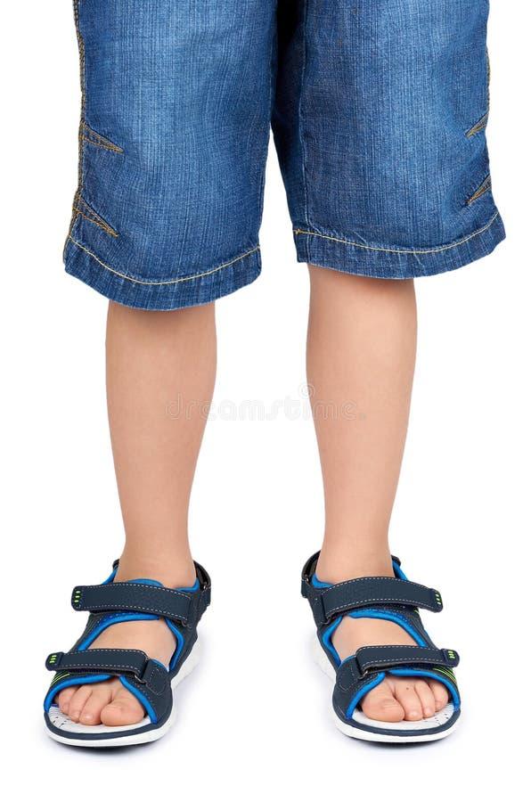 Sandalias del cuero de niños en la pierna aislada en un fondo blanco fotografía de archivo