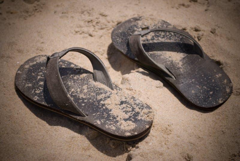 Sandalias en la arena imagen de archivo