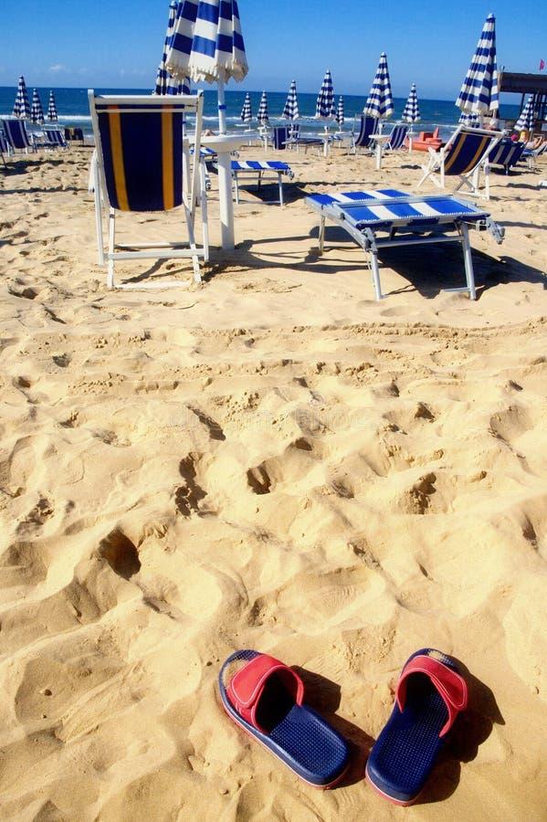Sandalias en una playa imagenes de archivo