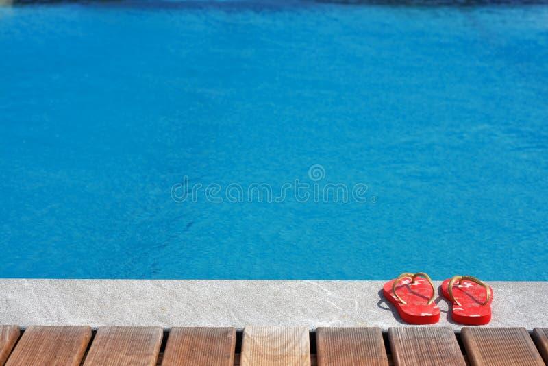 Sandalias por la piscina fotos de archivo