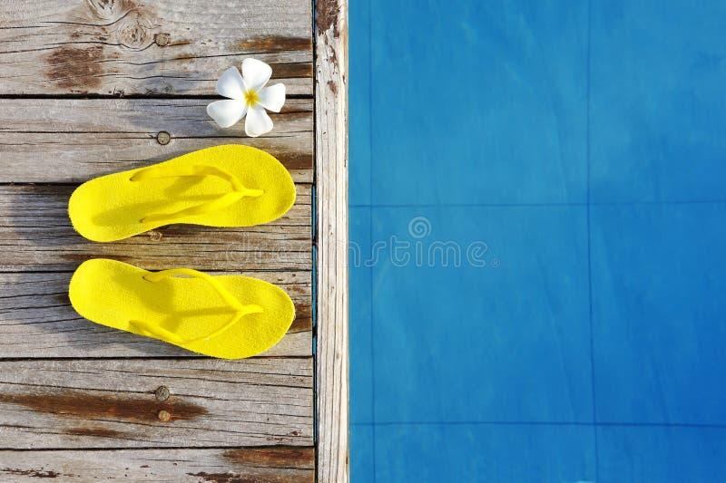 Sandalias por una piscina fotos de archivo