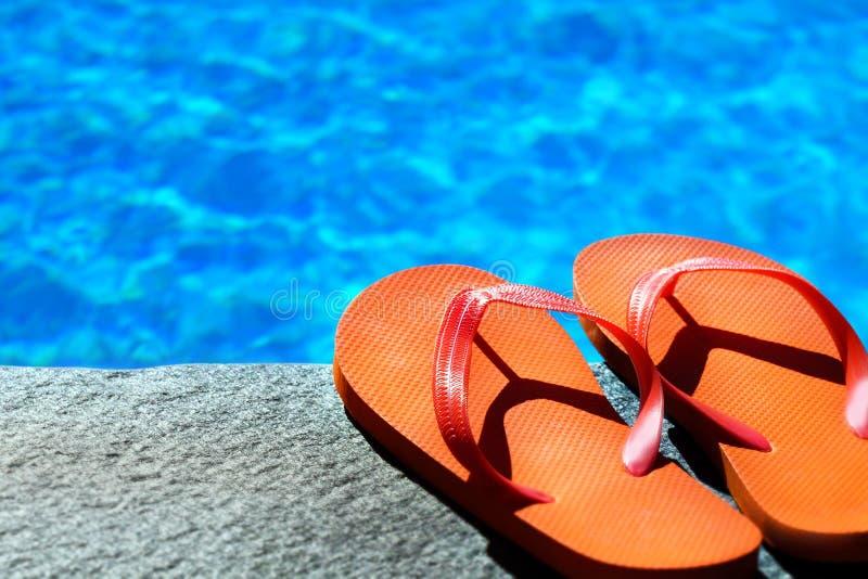 Sandalias por una piscina imagen de archivo