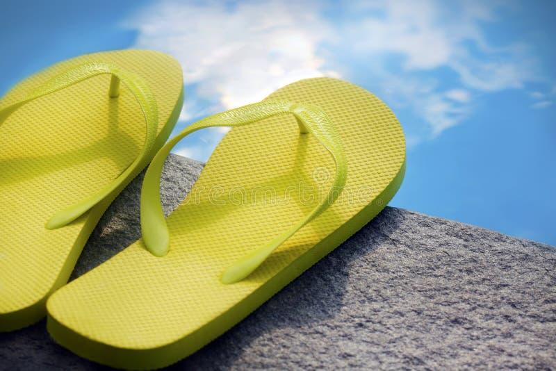 Sandalias por una piscina fotografía de archivo