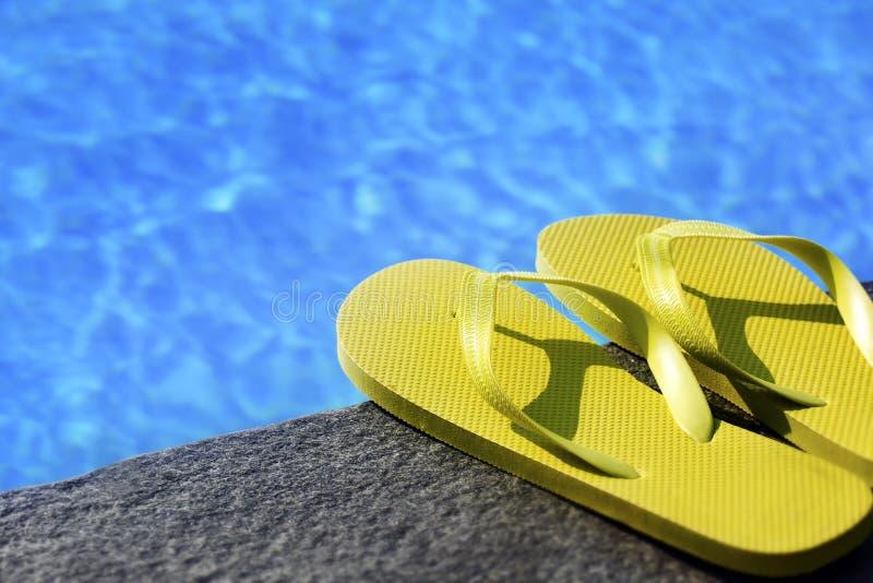 Sandalias por una piscina foto de archivo