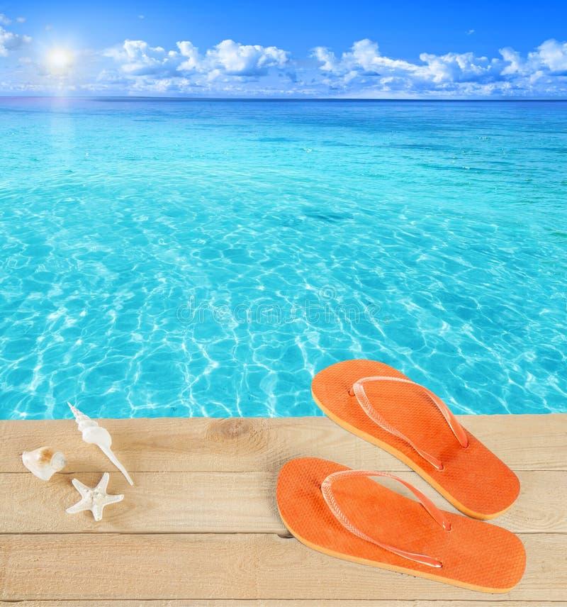 Sandalias por una piscina tropical imagenes de archivo