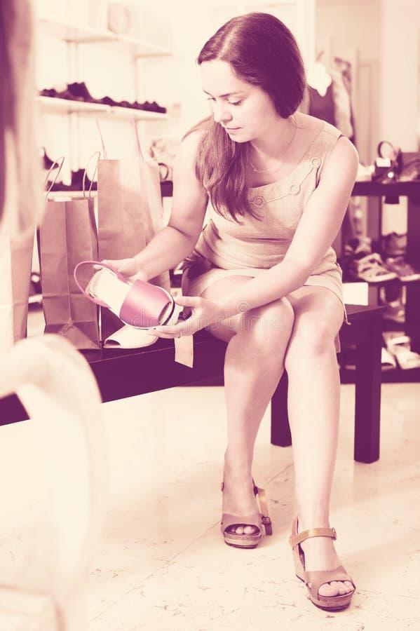 Sandalias que intentan de la morenita joven atractiva en tienda del calzado foto de archivo