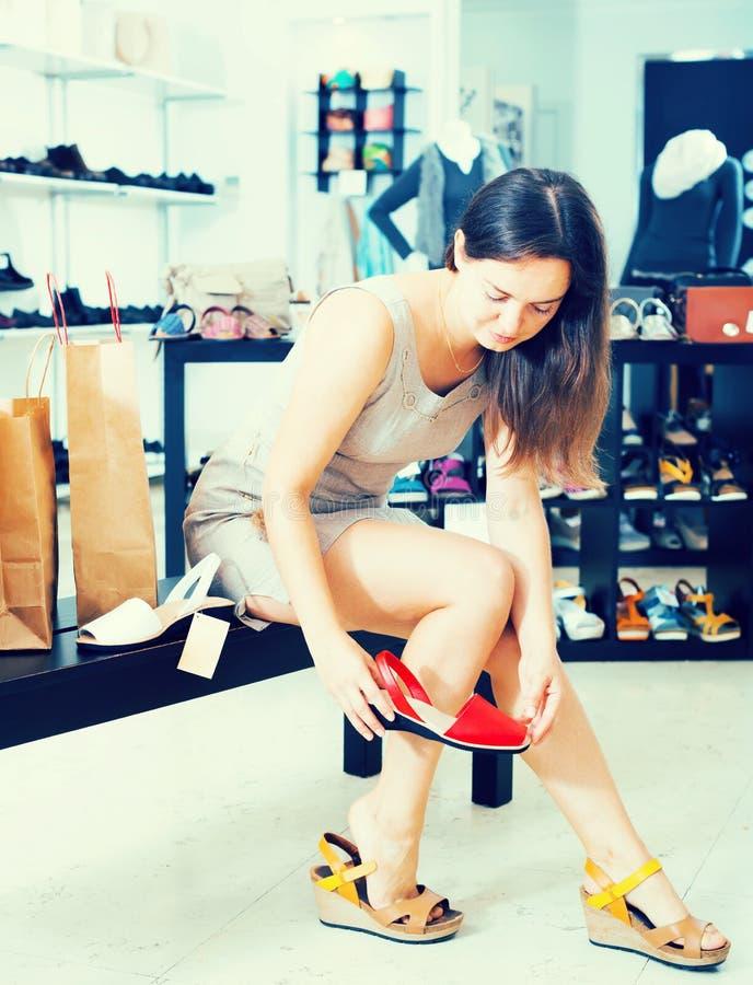 Sandalias que intentan morenas jovenes en tienda del calzado imagen de archivo libre de regalías