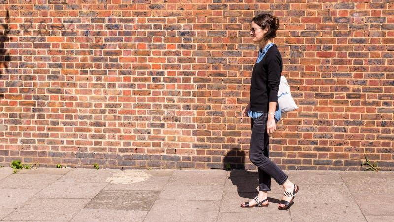 Sandalias que llevan de la mujer de moda joven, tejanos elásticos negros que caminan en la calle fotografía de archivo