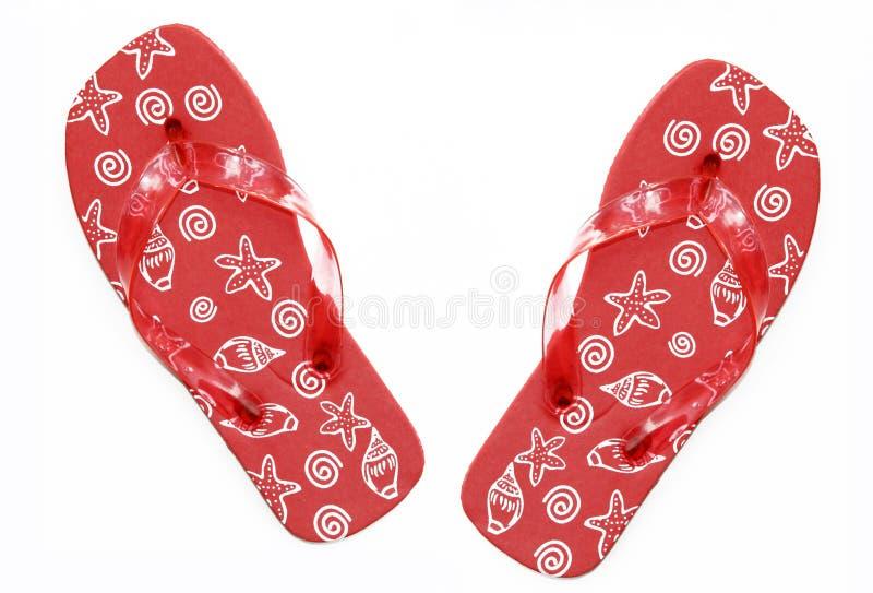 Sandalias rojas del fracaso de tirón del verano con diseño del shell del mar foto de archivo