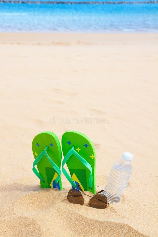 Sandalias verdes en la playa arenosa fotografía de archivo libre de regalías
