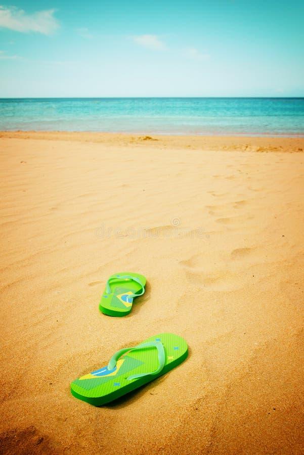 Sandalias verdes en la playa arenosa foto de archivo libre de regalías