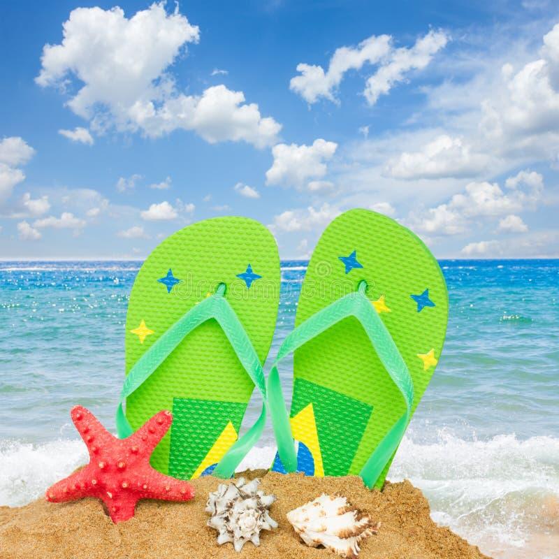 Sandalias y estrellas de mar en arena imagenes de archivo
