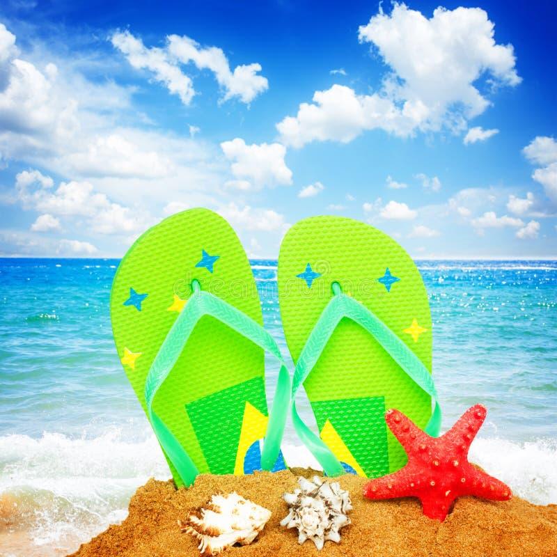 Sandalias y estrellas de mar en arena fotografía de archivo libre de regalías