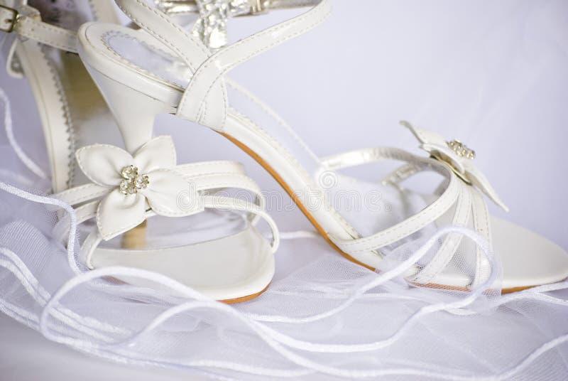 Sandalias y flores de la boda sobre velo fotografía de archivo libre de regalías