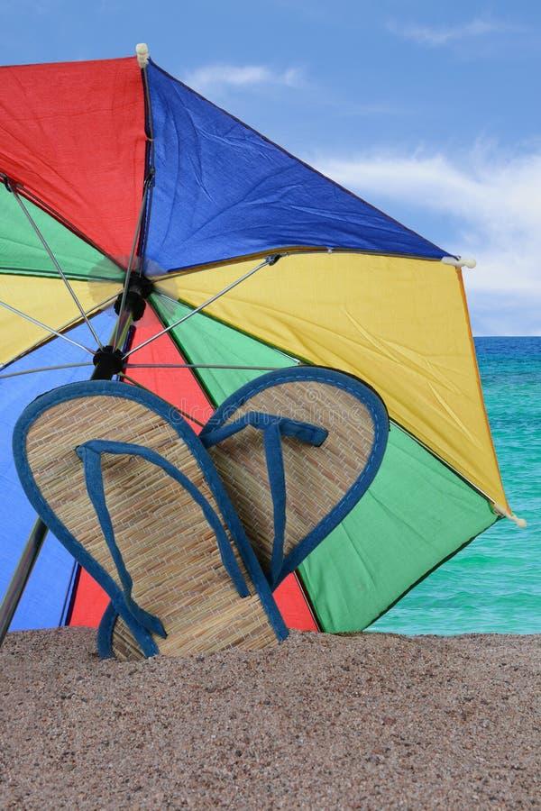 Sandalias y paraguas pegados en la arena fotos de archivo