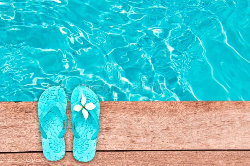 Sandals door een zwembad, de zomerconcept royalty-vrije stock fotografie