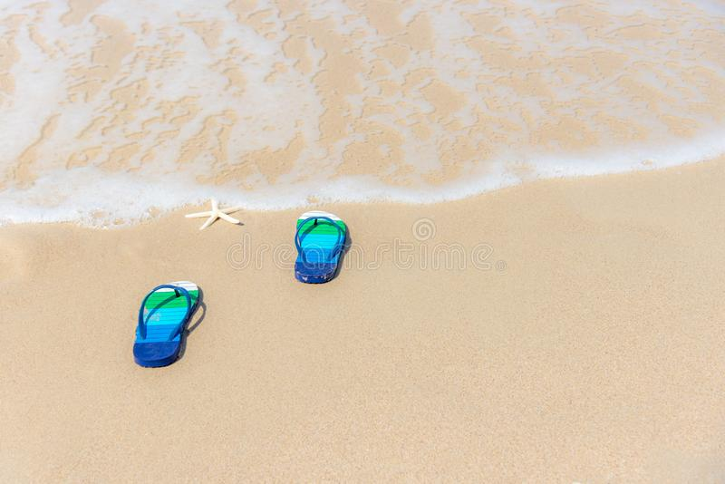 Sandals on a splashing water sandy ocean beach, relax and freedom. Summer vacation concept royalty free stock photos