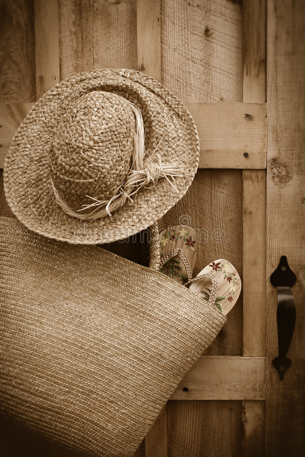 Sandals in sun purse/ Sepia tone. Pair of sandals hanging out of wicker purse with summer hat royalty free stock images