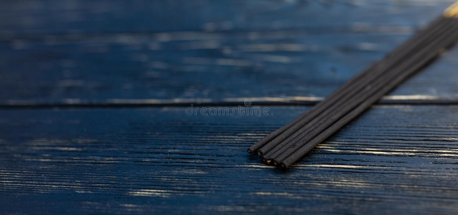 Sandalwood sticks on a black wooden table. Traditional Asian culture. Aromatherapy. With free space for text royalty free stock photo