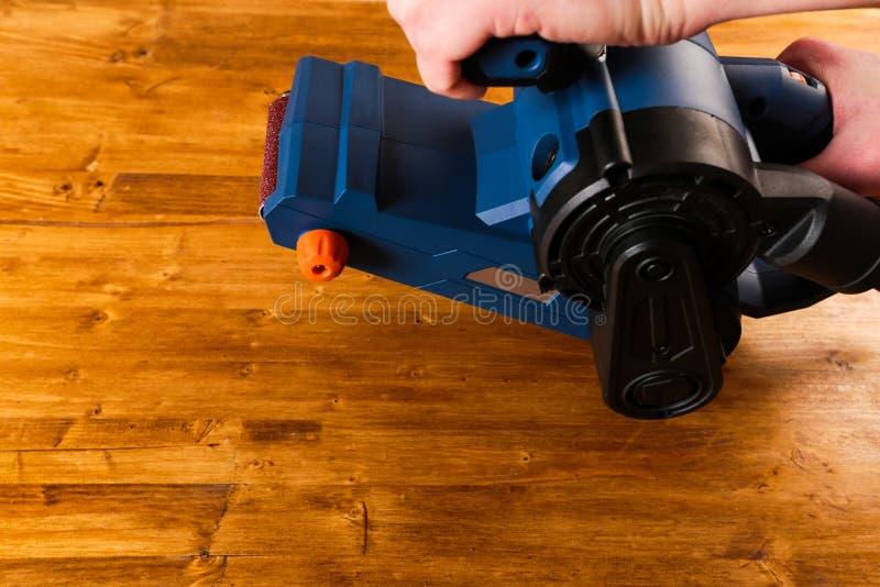 Инструмент Sandar с укомплектовывает личным составом руки на деревянной предпосылке стоковые изображения