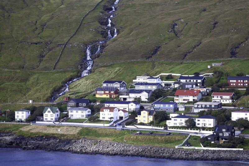 Sandavagur, Faroe Islands. View of Sandavagur village and tvatta waterfall across the fjord, Faroe Islands stock images