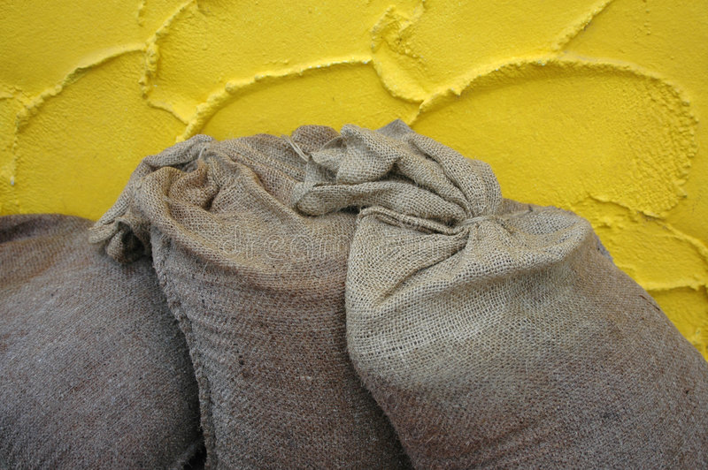 Sandbeutel gegen die gelbe Wand lizenzfreies stockbild