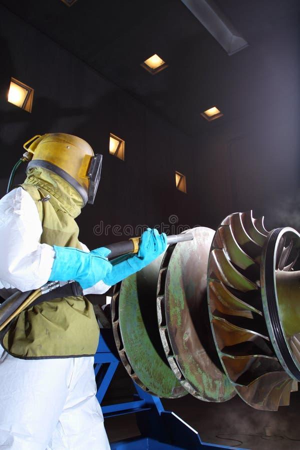 Sandblast. A worker sandblasting paint from turbine gear stock photography