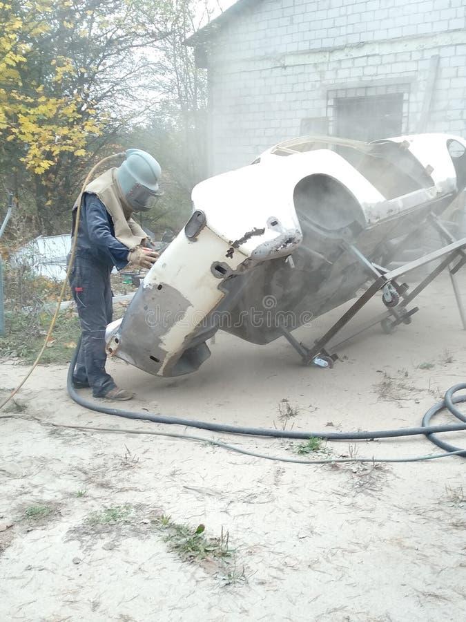 sandblasting the car body, rust removal royalty free stock photography