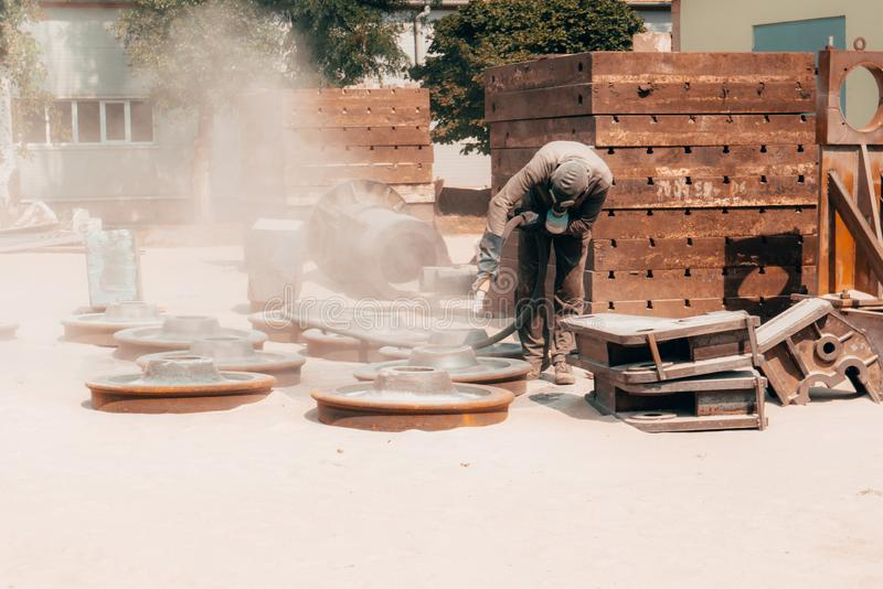 Sandblasting at an industrial plant, a worker knocks down oxide and dirty rust with sand under air pressure from a hose.  royalty free stock photo
