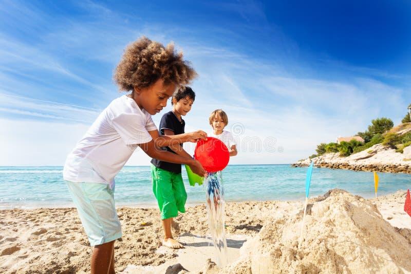 Sandcastle здания мальчика с друзьями на пляже стоковые фотографии rf