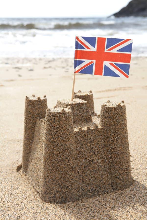 Sandcastle на пляже с флагом Юниона Джек стоковое изображение