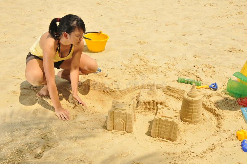Sandcastle asiático novo do edifício da menina pela praia fotografia de stock royalty free