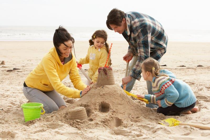 Sandcastle do edifício da família na praia do inverno fotos de stock royalty free